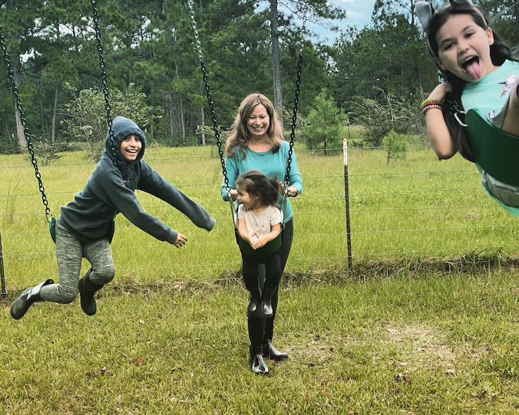 picture of sara pushing child on swing