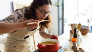 Woman tasting her healthy soup recipe